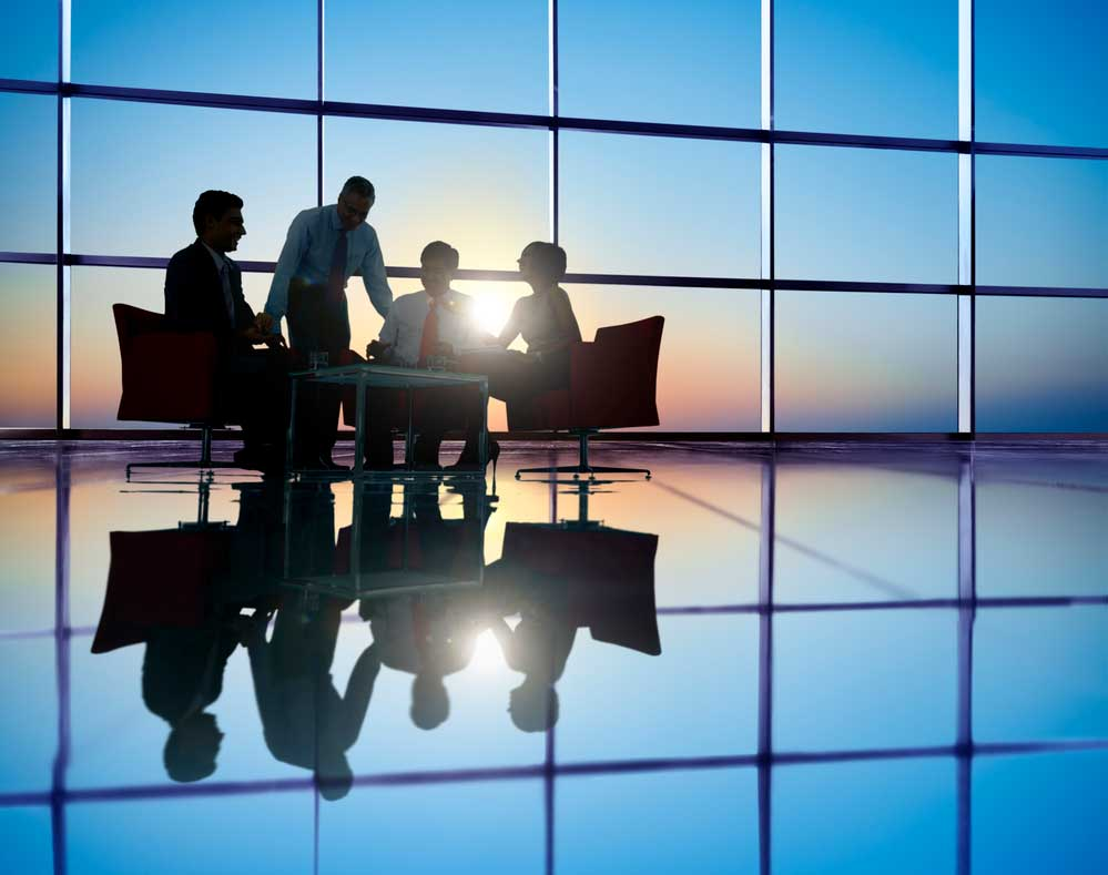 corporate setting with 4 people sitting in front of a wall of windows while the sun is setting